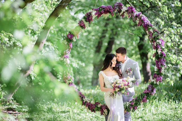 Bride and groom pose behind large circle of lilac in the garden Free Photo