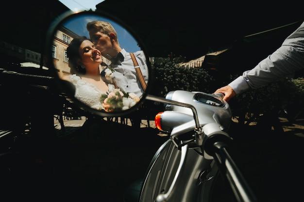 ヴィンテージのスクーターでポーズをとる新郎新婦 無料写真