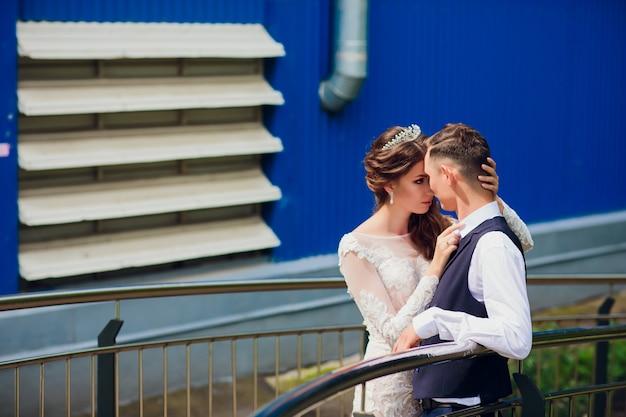 Жених и невеста гуляя в город, день свадьбы, принципиальная схема замужества. жених и невеста в городской предпосылке. молодая пара собирается на лестнице в день свадьбы. Premium Фотографии