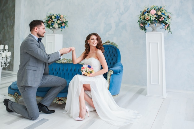 Bride in beautiful dress and groom in gray suit sitting on sofa indoors. trendy wedding style Premium Photo