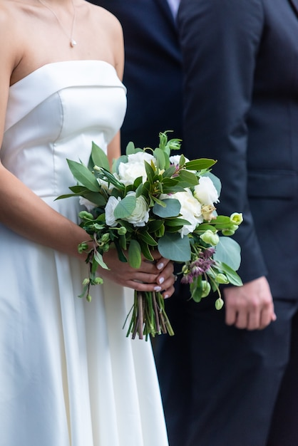 A bride in a beautiful white wedding dress holding a bridal bouquet standing next to the groom Free Photo