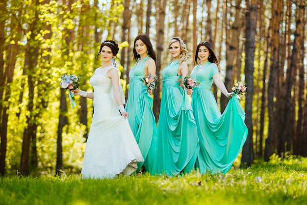 Bride and bridesmaids with wedding bouquets. sunny wedding reception joyful moment. Free Photo