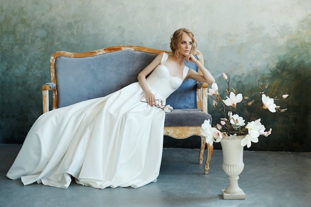 Bride in a chic long dress lying on the sofa couch. white wedding dress Premium Photo