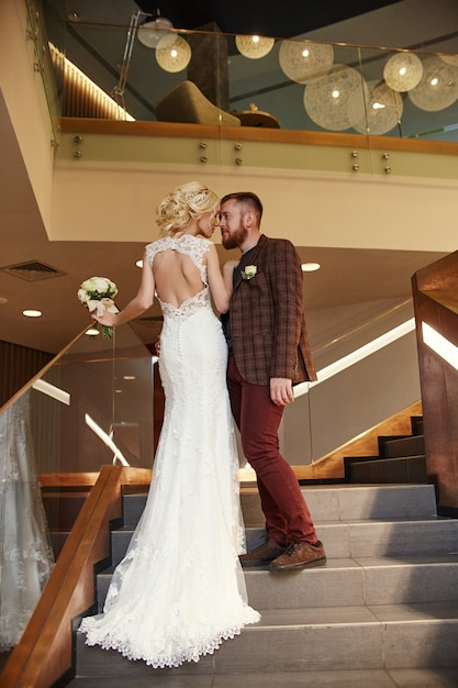 Bride in a chic long dress with a train and groom Premium Photo