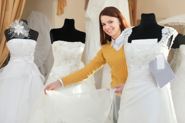 Bride chooses wedding gown at bridal boutique Photo | Free Download