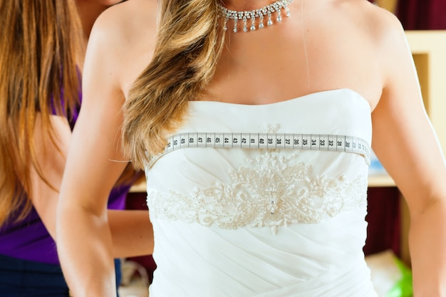Bride at the clothes shop for wedding dresses, she is choosing a dress Premium Photo