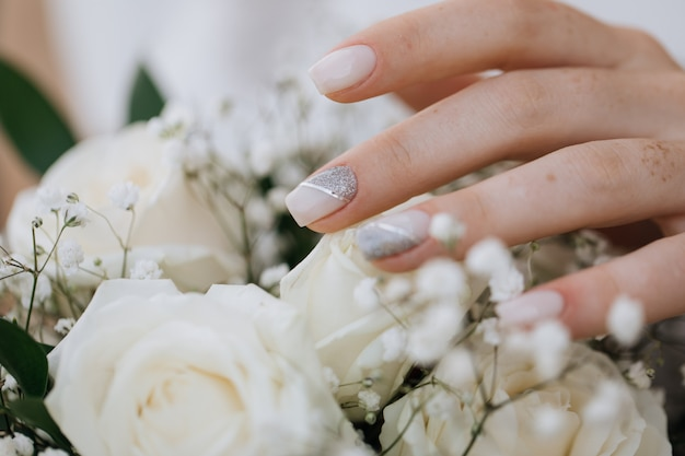 Bride demonstrates her manicure over wedding bouquet Free Photo