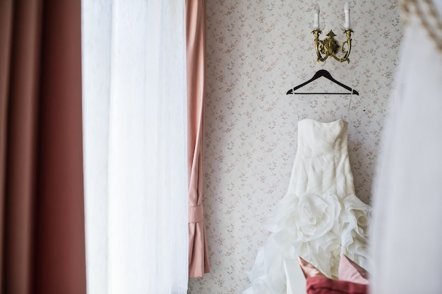 Bride dress on a hanger in the elegant interior of the hotel Premium Photo