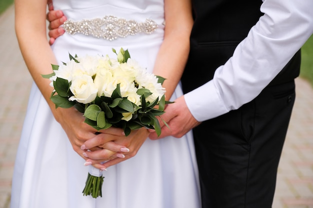The bride in an elegant wedding dress is holding a beautiful bouquet of white roses and chrysanthemums and green leaves. embrace the newlyweds, the hands of the bride and groom close-up, outdoors. Premium Photo