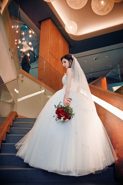 Bride in elegant wedding dress standing on stairs Premium Photo