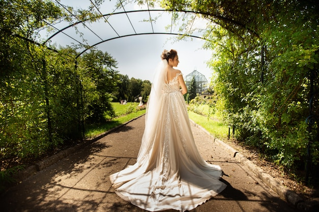 Bride in fashion wedding dress on natural background. a beautiful woman portrait in the park. back view Premium Photo