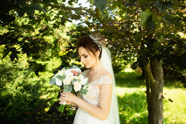 Bride in fashion wedding dress on natural background. a beautiful woman portrait in the park Premium Photo