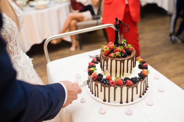 The bride and groom cut the chocolate wedding cake. Premium Photo