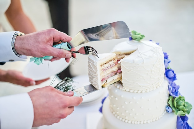 Bride and groom cut white wedding cake decorated with blue flowers Premium Photo