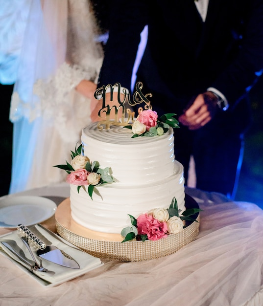 Bride And Groom Cut White Wedding Cake With Pink Flowers