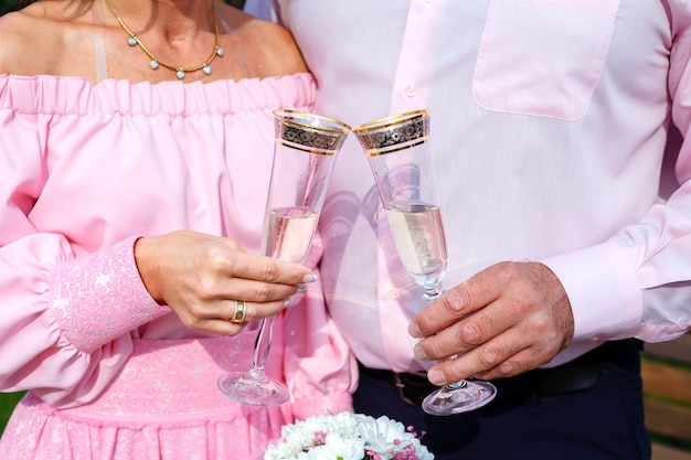 Bride and groom holding champagne glasses and bridal bouquet Premium Photo