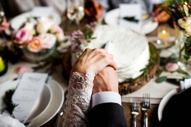 Bride and groom holding hands each other on wedding reception Premium Photo