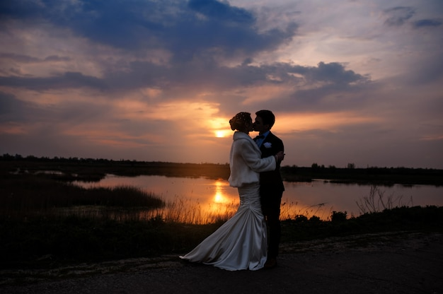 Bride and groom kissing at sunset  beautiful romantic married couple Premium Photo