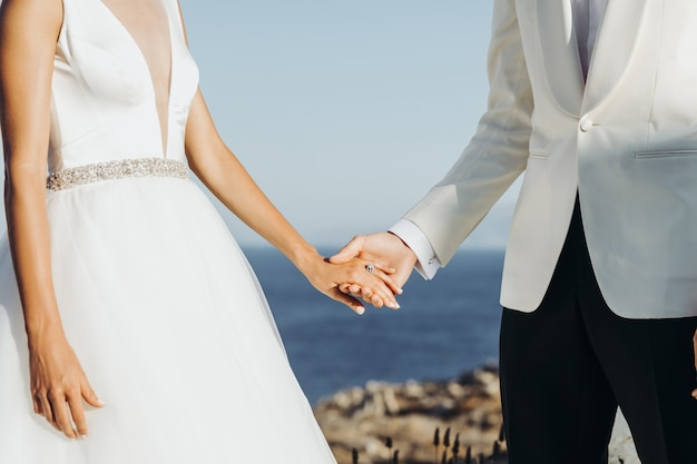 Bride and groom in light summer clothes hold each other hands during the ceremony Free Photo