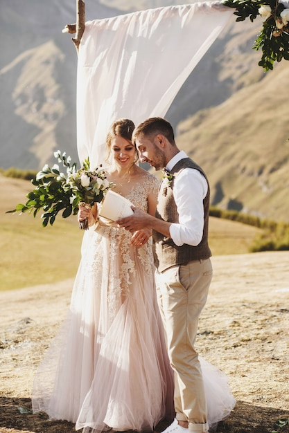 Bride and groom look lovely during the wedding ceremony on the top of the mountain Premium Photo