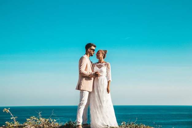 Bride and groom posing on the cliff behind blue sky and sea Free Photo