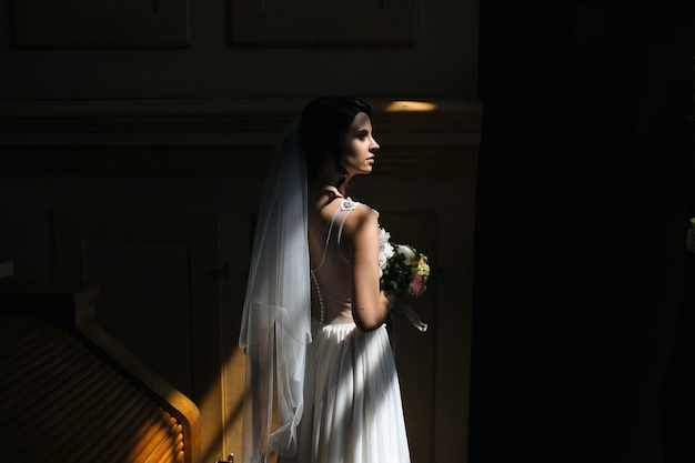 Bride and groom posing in the dimly lit room Free Photo
