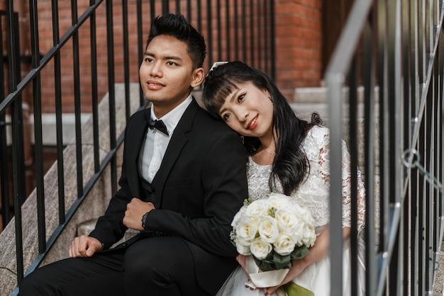 Sposa e sposo che propongono insieme sui gradini Foto Gratuite
