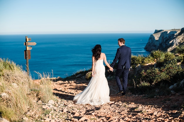 Bride and groom walking on the beach and holding each other's hand. Premium Photo