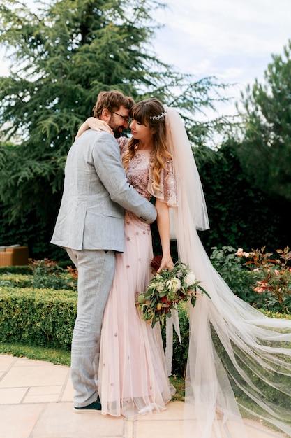 Sposa e sposo al giorno delle nozze camminando all'aperto sulla natura primaverile. newlywed felice donna e uomo che abbracciano nel parco verde. coppia di innamorati matrimonio. Foto Gratuite