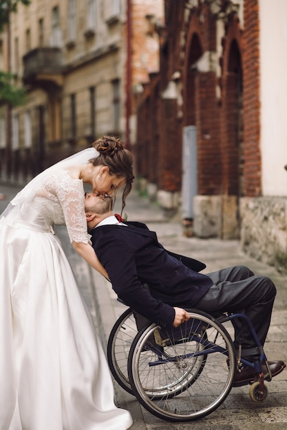 Bride and groom on the wheelchair pose on old european street Free Photo