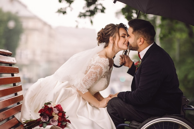 Bride and groom on the wheelchair sit kissing on the bench in the park Free Photo