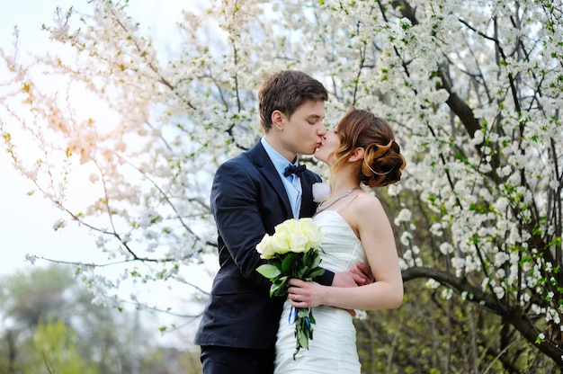 Bride and groom with a bouquet of walking in the summer park Premium Photo