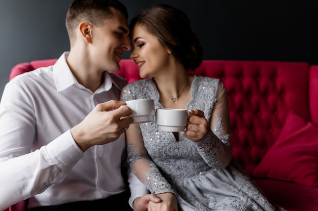 The bride and groom with coffee cups hug each other Free Photo