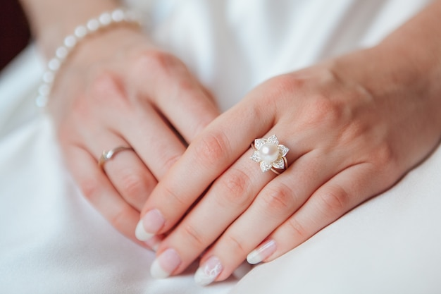 Bride hand with diamond ring and pearl bracelet on white dress Free Photo