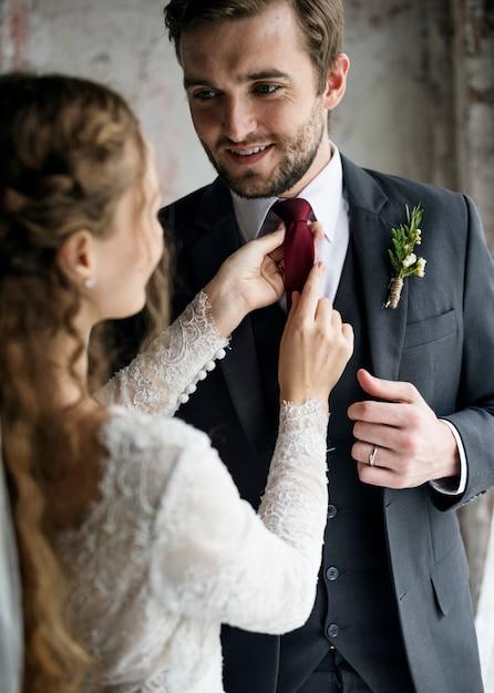 Bride helping groom dressing up for wedding ceremony Premium Photo