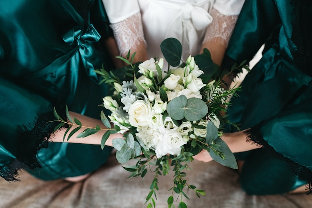 The bride and her friends hold a wedding bouquet Free Photo