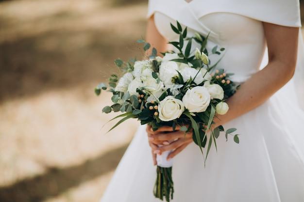Sposa che tiene il suo bouquet da sposa Foto Gratuite