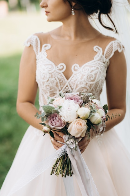 Bride holds the beautiful bridal bouquet with roses and peonies Free Photo