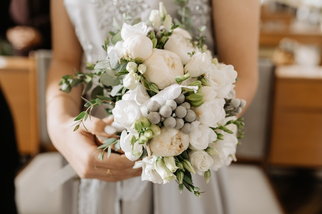 Bride holds the beautiful bridal bouquet with white peonies and green decor Free Photo