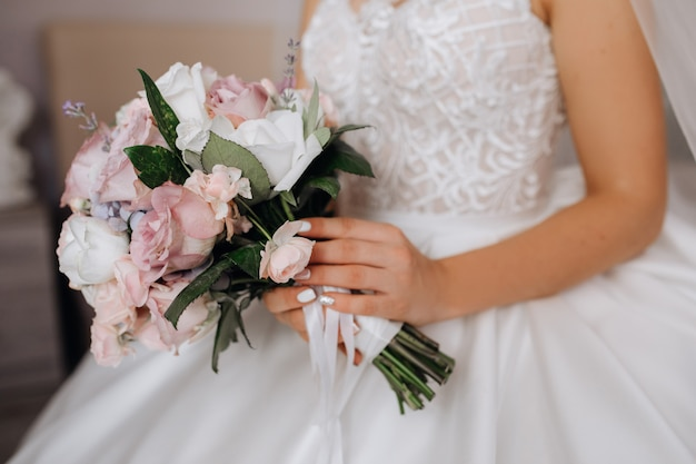 Bride holds the beautiful bridal bouquet with white and pink roses Free Photo