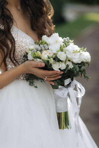 Bride holds the beautiful bridal bouquet with white roses and peonies Free Photo