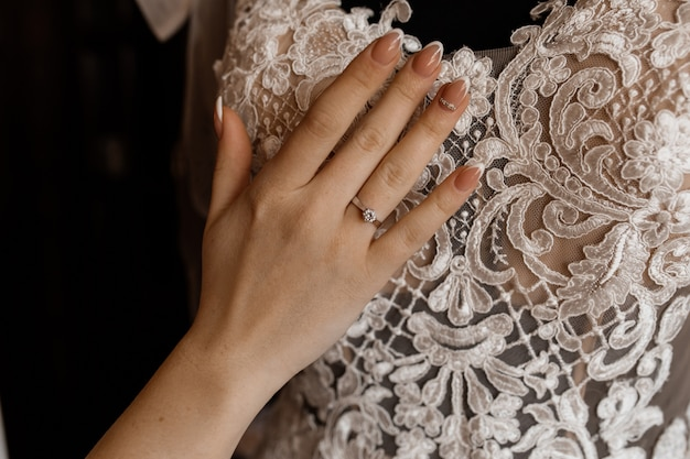 Bride holds her hand on hanged bridal dress Free Photo