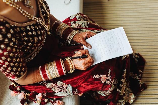 伝統的なインドの服の花嫁は、紙に彼女の誓いを書いています 無料写真