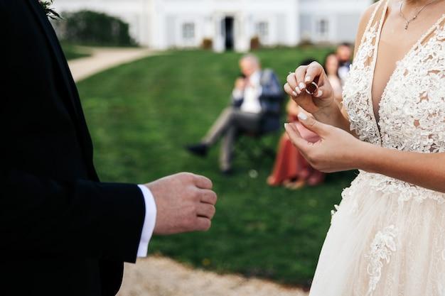 신부는 신랑의 손가락에 결혼 반지를 배치합니다 무료 사진