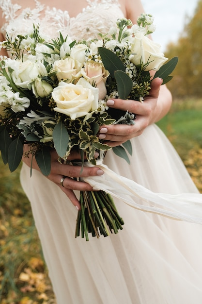 The bride is holding a beautiful white wedding bouquet. close up. autumn. Premium Photo