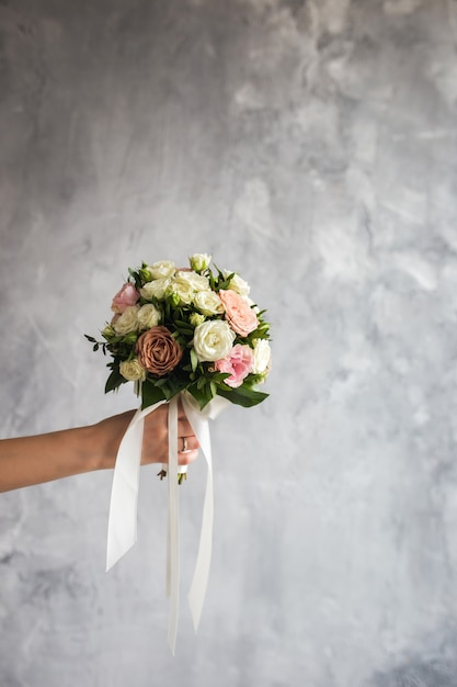 The bride is holding a wedding bouquet on a gray Premium Photo