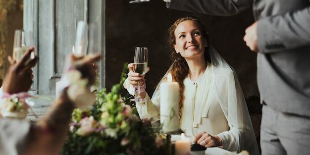Bride listening to a speech at wedding reception table Premium Photo