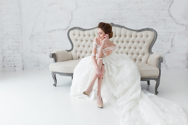 Bride in long dress sitting on sofa indoors in white studio interior like at home. Free Photo