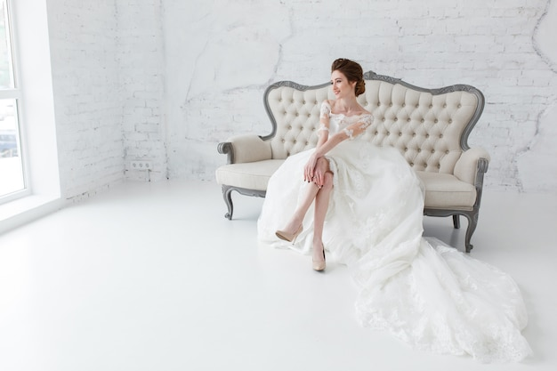 Bride looking out the window, she waits for the groom sitting on big classic sofa. Free Photo