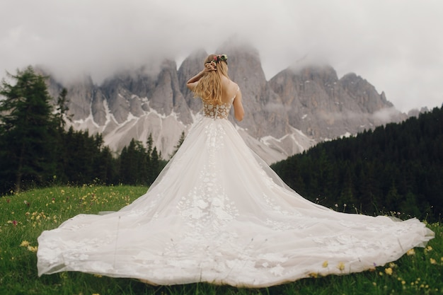 Bride in a luxury dress stands before beautiful mountain landscape Free Photo